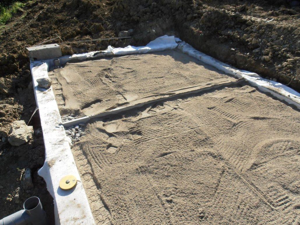 Pose du sable d'assainissement dans le filtre planté